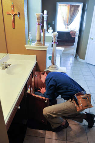 Mike Krumel looks over bathroom plumbing while inspecting a home in Helotes. Krumel, who had a long career as a manufacturers representative for homebuilding products before retiring, now owns a Pillar to Post franchise that specialize in home inspections. Photo: Robin Jerstad
