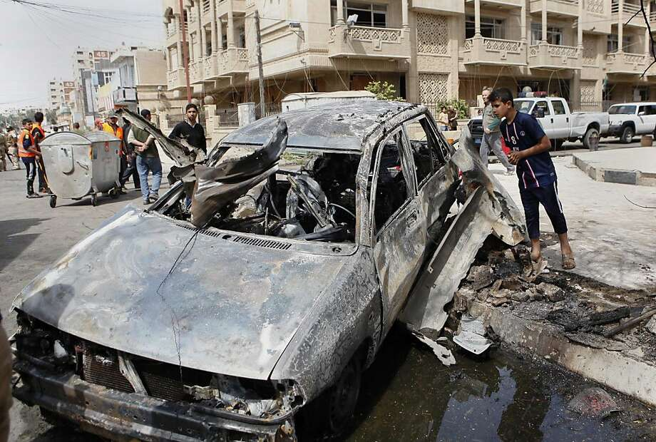 People check out a car destroyed in a bombing near a gate to the heavily fortified Green Zone in Baghdad. Nearly 20 attacks were unleashed around the capital on the eve of the 10th anniversary of the U.S. invasion of Iraq. It was the bloodiest day in the country since Sept. 9, when 92 people were slain. Photo: Hadi Mizban, Associated Press