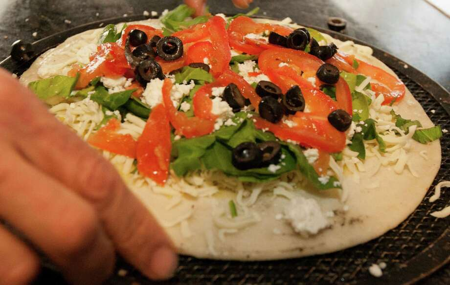 Organic spinach, roma tomatoes and Italian black olives make up this pizza. Photo: J. Patric Schneider, Freelance / © 2013 Houston Chronicle
