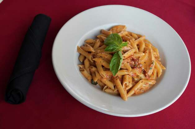 The gluten free dish has penne pasta with prosciutto, tomato, and vodka sauce. Photo: J. Patric Schneider, Freelance / © 2013 Houston Chronicle