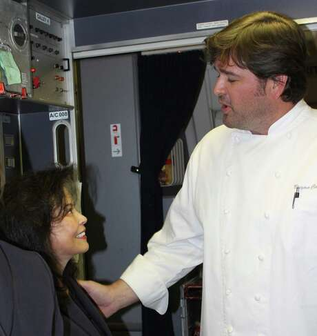 Bryan Caswell, right, interacts with flight attendants aboard a United Airlines flight from Newark, N.J., to Hong Kong on March 2, 2013.  Caswell is a member of United's Congress of Chefs. Photo: Syd Kearney