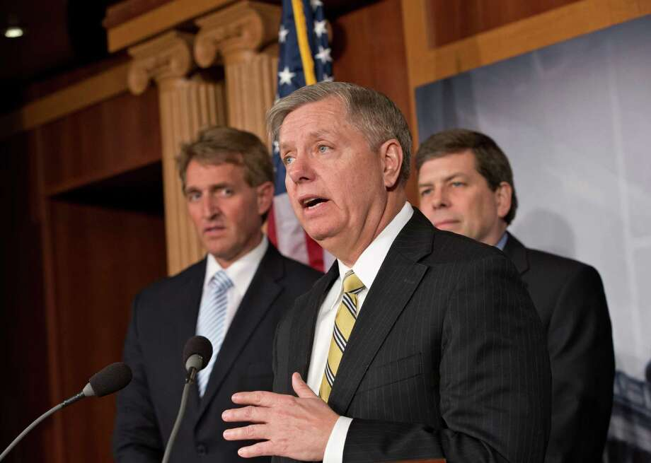 Sen. Lindsey Graham, R-S.C., center, joined by Sen. Jeff Flake, R-Ariz., left, and Sen. Mark Begich, D-Alaska, right, meet with reporters to talk about a bill they are introducing to keep guns from being legally purchased by people with serious mental health problems, on Capitol Hill in Washington, Wednesday, March 6, 2013. (AP Photo/J. Scott Applewhite) Photo: J. Scott Applewhite, STF / AP