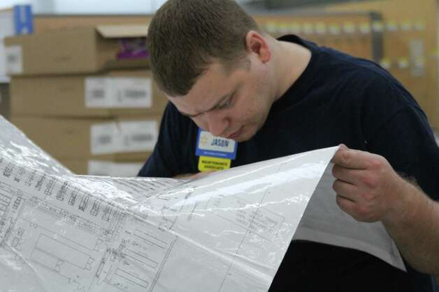 "Jason Parsons, 27, maintainance associate, pores over a Walmart store map as he helps prepare the Helotes site for its April 10 opening. It's his first job, he says, and, as a college student, he says, the company does ""really well working with a college schedule."" Photo: Lauri Gray Eaton / Northwest Weekly"