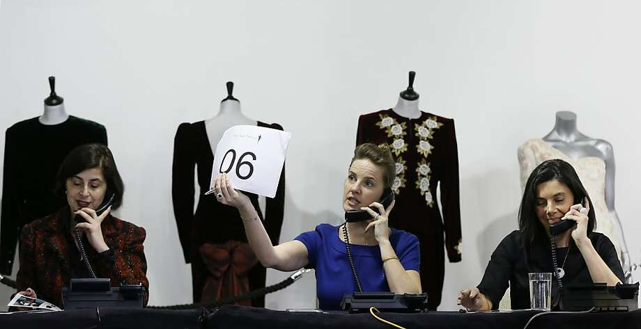 The auction house staff takes telephone bids on some of Princess Diana's most notable gowns. Photo: Kirsty Wigglesworth, Associated Press