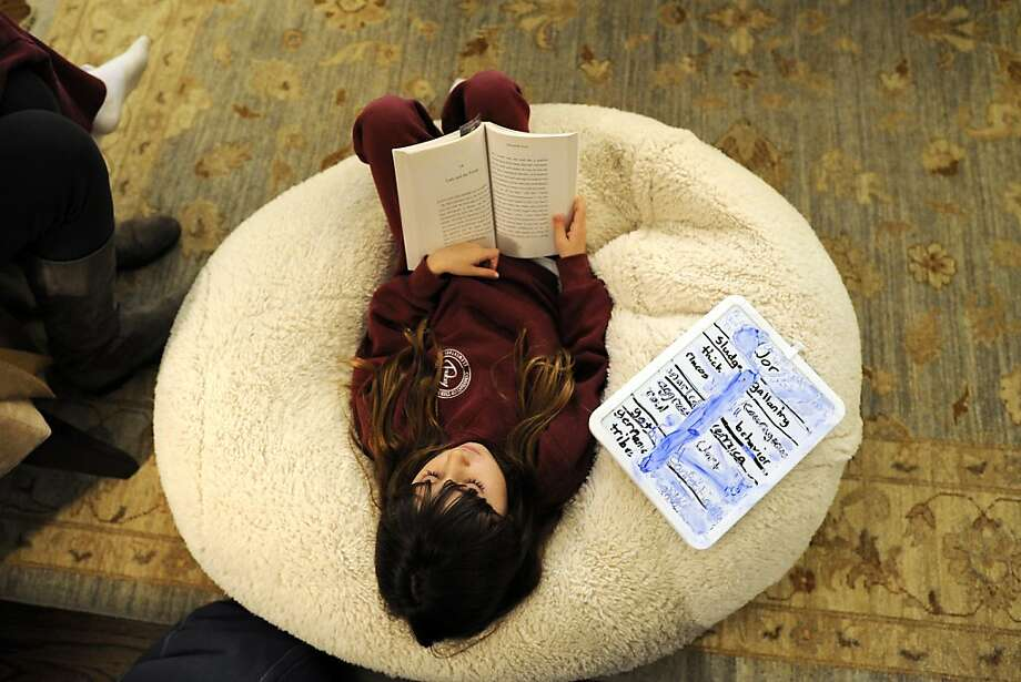 Sasha Carney, 8, reads along with her book club as she relaxes in a beanbag chair during a meeting in San Francisco. Photo: Michael Short, Special To The Chronicle