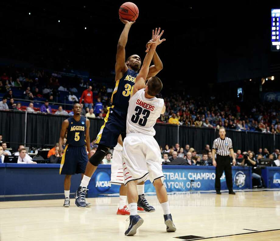 Lamont Middleton #30 of the North Carolina A&T Aggies attempts a shot in the first half against John Caleb Sanders #33 of the Liberty Flames. Photo: Gregory Shamus, Getty Images / 2013 Getty Images
