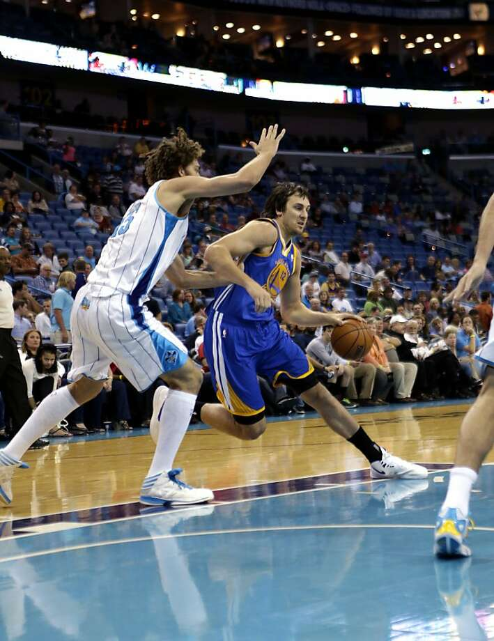 Warriors center Andrew Bogut (12) drives against the Hornets' Robin Lopez (15) in Monday's victory. Photo: Gerald Herbert, Associated Press