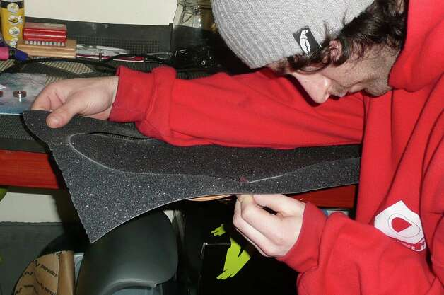 With the grip tape now attached to Berlic's skateboard, Garan carefully cuts off the excess tape around the board edges. Photo: Anne W. Semmes