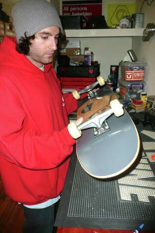 Garan prepares to hand over the completed redo of Oliver Berlic's skateboard - usually a 15-20 minute process. Some of his customers, Garan says, like to do the work themselves under his watchful eye. Photo: Anne W. Semmes