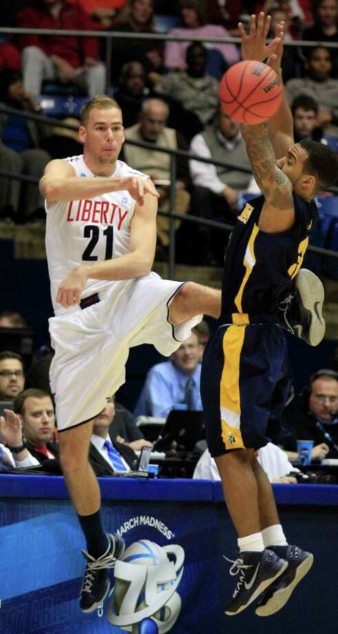 Liberty center Joel Vander Pol (21) passes around North Carolina A&T guard Jeremy Underwood in the first half of a first round NCAA college basketball tournament game, Tuesday, March 19, 2013, in Dayton, Ohio. (AP Photo/Skip Peterson) Photo: Skip Peterson, Associated Press / FR23879 AP