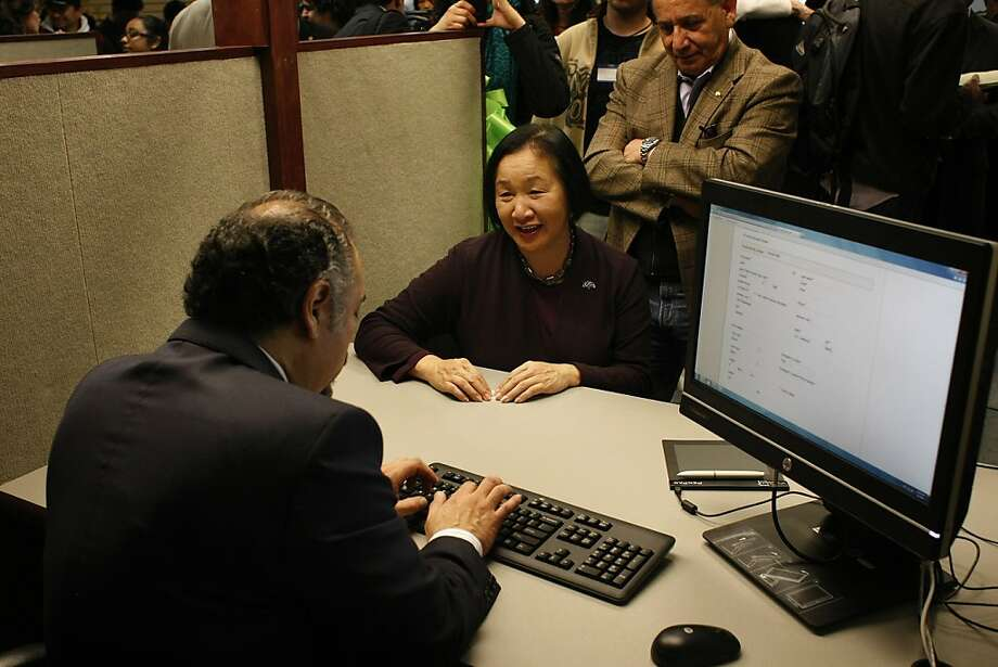 Oakland Mayor Jean Quan (center) registers for an Oakland municipal identification card with Jaime Suriano, operations manager for the company that set up the city's card program. Photo: James Tensuan, The Chronicle