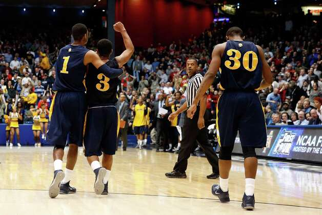 Adrian Powell #1, Jeremy Underwood #3 and Lamont Middleton #30 of the North Carolina A&T Aggies celebrate after they defeated Liberty. Photo: Gregory Shamus, Getty Images / 2013 Getty Images