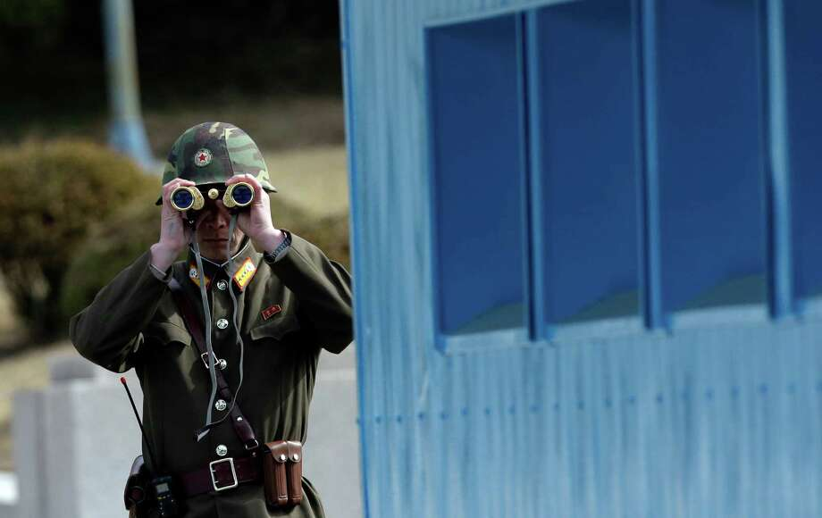 A North Korean soldier looks at the southern side through a pair of binoculars at the border village of the Panmunjom (DMZ) that separates the two Koreas since the Korean War, in Paju, north of Seoul, South Korea, Tuesday, March 19, 2013. The United States is flying nuclear-capable B-52 bombers on training missions over South Korea to highlight Washington's commitment to defend an ally amid rising tensions with North Korea, Pentagon officials said Monday.(AP Photo/Lee Jin-man) Photo: Lee Jin-man