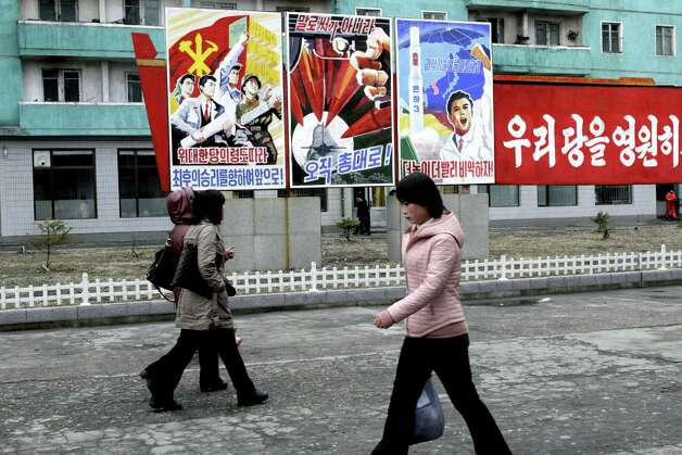 "North Koreans walk past posters reading ""Forward to the ultimate victory under the leadership of the great party!"" left,  ""not with words but with arms,"" center, and ""Higher, faster,"" right, on Tuesday, March 19, 2013, on a street in Phyongchon District in Pyongyang, North Korea.  The banner partially shown at right reads in its entirety ""Let's strengthen and enhance our party as the party of Kim Il Sung and Kim Jong Il!"" (AP Photo/Jon Chol Jin) Photo: Jon Chol Jin"