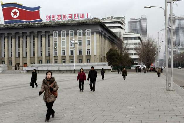 "People walk through Kim Il Sung Square, in Pyongyang, North Korea on Tuesday, March 19, 2013. The writing on top of the building reads ""Hurrah to the DPRK,"" the acronym for North Korea's formal name, the Democratic People's Republic of Korea. (AP Photo/Jon Chol Jin) Photo: Jon Chol Jin"