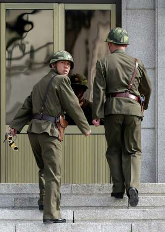Two North Korean soldiers walk up the stairs after their patrol at the border village of the Panmunjom (DMZ) that separates the two Koreas since the Korean War, in Paju, north of Seoul, South Korea, Tuesday, March 19, 2013. The United States is flying nuclear-capable B-52 bombers on training missions over South Korea to highlight Washington's commitment to defend an ally amid rising tensions with North Korea, Pentagon officials said Monday. (AP Photo/Lee Jin-man) Photo: Lee Jin-man