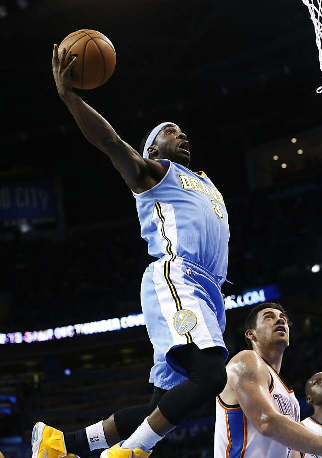 Denver guard Ty Lawson soars over Thunder forward Nick Collison in the first half in Oklahoma City. Lawson scored 25 points in the Nuggets' win. Photo: Sue Ogrocki, Associated Press