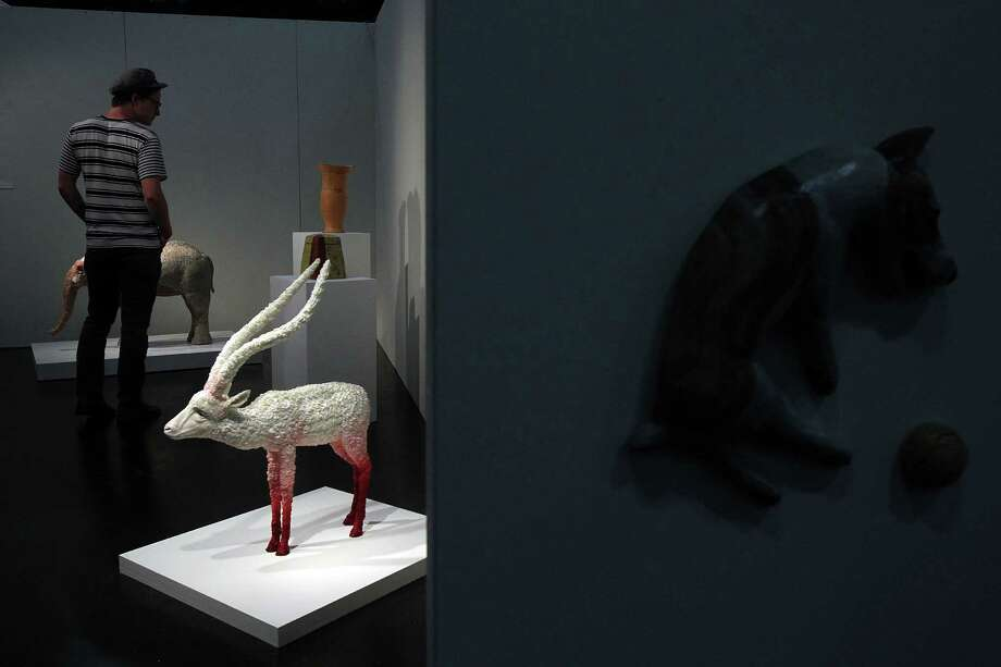 Austin Riddle views artwork in the Emerging Artist display during the 47th Annual National Council on Education for the Ceramic Arts at George R. Brown Convention Center on Tuesday, March 19, 2013, in Houston. Photo: Mayra Beltran, Houston Chronicle / © 2013 Houston Chronicle