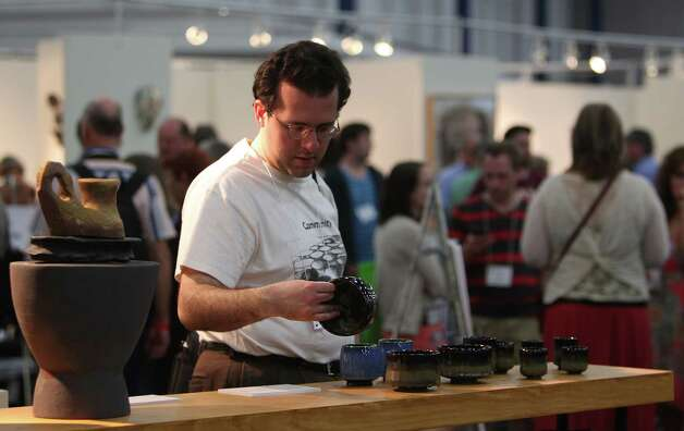 Jonathan Gastello views ceramic pieces during the 47th Annual National Council on Education for the Ceramic Arts at George R. Brown Convention Center on Tuesday, March 19, 2013, in Houston. Photo: Mayra Beltran, Houston Chronicle / © 2013 Houston Chronicle