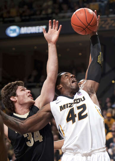 FILE- In this Jan. 26, 2013, file photo, Missouri's Alex Oriakhi, right, pulls down a rebound in fro