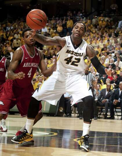 Missouri's Alex Oriakhi, right, loses control of the ball in front of Arkansas' Coty Clarke, left, d