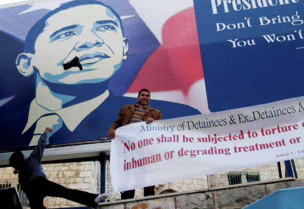 Palestinian activists throw shoes at a poster of US President Barack Obama in the West Bank city of Bethlehem, Monday, March 18, 2013. Some two dozen Palestinian activists protested the upcoming Obama visit. Obama's trip to Jerusalem and the West Bank will take place March 20-22, and it is the U.S. leader's first trip to the region as president, and his first overseas trip since being reelected. (AP Photo/Nasser Shiyoukhi) Photo: Nasser Shiyoukhi