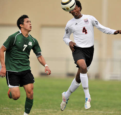 Churchill's Gideon Farr (4) pushes the ball upfield against Reagan's Luis Hernandez during their District 26-5A championship soccer match Tuesday evening. Photo: Robin Jerstad, For The San Antonio Express-News