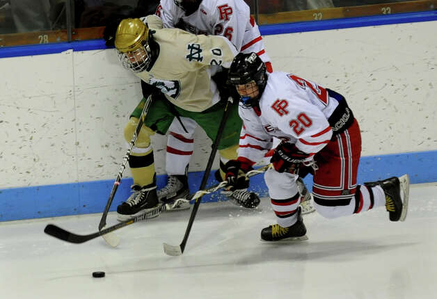 Fairfield Prep's #26 Matt McKinney, in back, tangles with Notre Dame of West Haven's #20 Kyle Lynch as #20 Tim Edmonds chases down the puck, during CIAC Division I boys hockey final action at Ingalls Rink in New Haven, Conn. on March 19, 2013. Photo: Christian Abraham / Connecticut Post