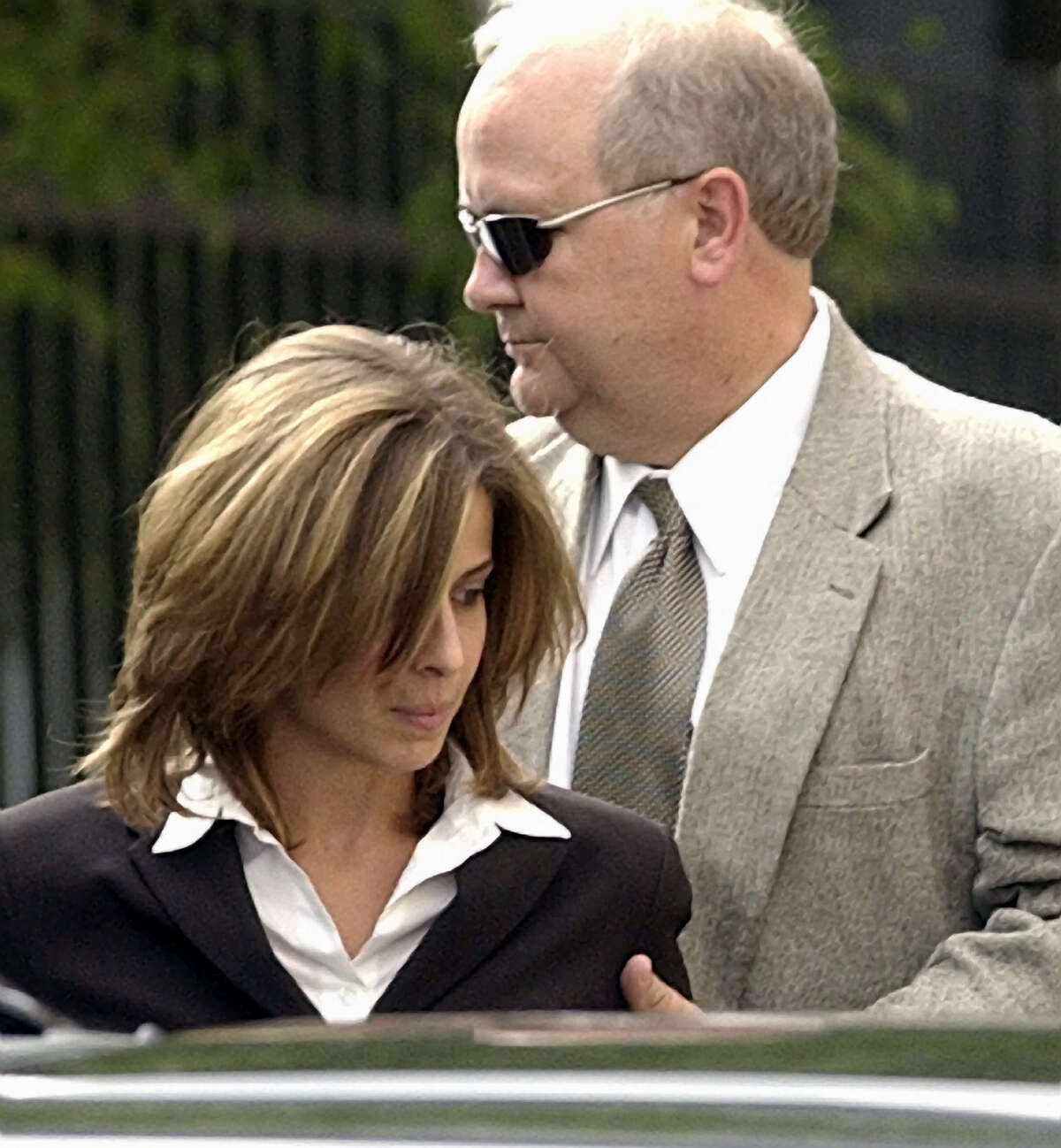 Helen Christine Sharkey, left, a former member of Dynegy's risk control and deal structure groups, is escorted into the Federal Courthouse, Thursday, June 12, 2003, in Houston. Sharkey is one of three former Dynegy Inc. executives charged in a federal indictment unsealed Thursday with creating an Enronesque deal in 2001 used to wrongly boost cash flow and cut taxes to counteract Wall Street worries about the company's financial health. (AP Photo/David J. Phillip)