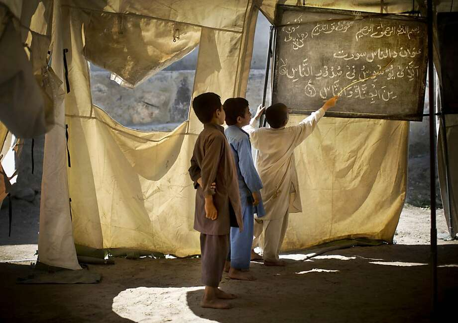 Afghan boys study at a makeshift school in the village of Budyali, Nengarhar Province, Afghanistan, Tuesday, March 19, 2013. Providing education to Afghan boys and girls was a priority after the collapse of the Taliban, who refused to educate girls. (AP Photo/Anja Niedringhaus) Photo: Anja Niedringhaus, Associated Press