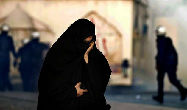 A Bahraini woman reacts to tear gas during clashes with riot police in Bilad al-Qadeem, Bahrain, on Tuesday, March  19, 2013. Clashes erupted after police dispersed a protest held to mark the anniversary of a protester's death in earlier clashes. (AP Photo/Hasan Jamali) Photo: Hasan Jamali, Associated Press