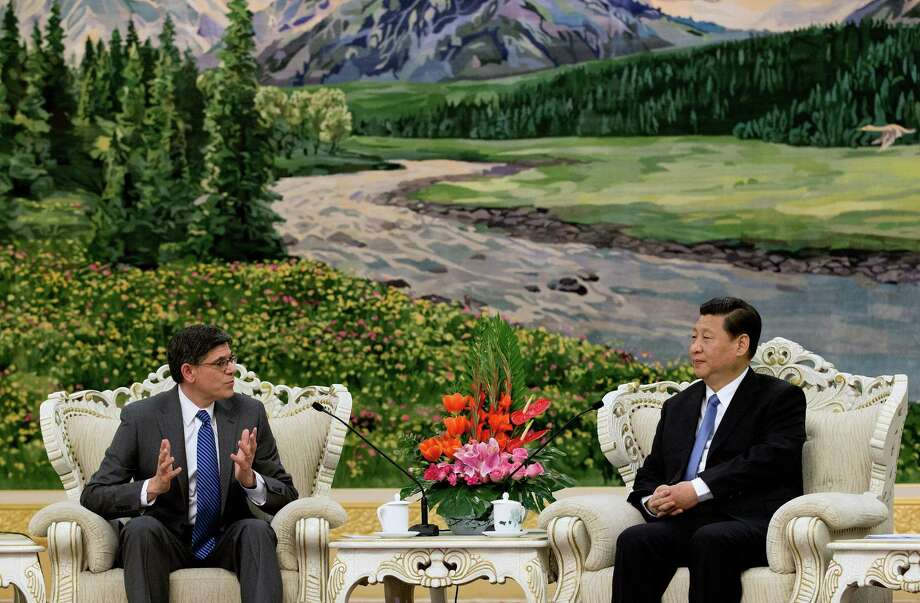 Newly appointed U.S. Treasury Secretary Jacob Lew, left, and Chinese President Xi Jinping, right, chat during their meeting at the Great Hall of the People in Beijing Tuesday, March 19, 2013. (AP Photo/Andy Wong, Pool) Photo: Andy Wong