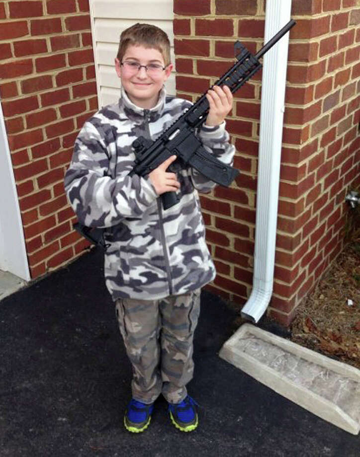 This undated photo provided by Shawn Moore shows his son Josh, 11, holding a rifle his father gave him as a birthday present, at their home in Carneys Point, N.J.  The Moore family claims this photo, posted on Facebook, led the state's child welfare agency to the family's house, Friday, March 15, 2013, demanding to be let inside to inspect their guns. (AP Photo/Shawn Moore) Photo: Shawn Moore