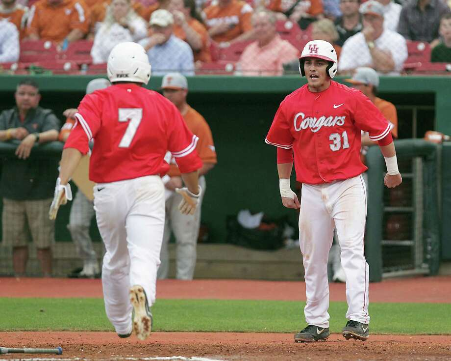 The University of Houston's Jacob Campbell right, cheers on teammate Frankie Ratcliff left, after the pair scored runs against the University of Texas during the second inning of college baseball game action at the University of Houston's Cougar Field Tuesday, March 19, 2013, in Houston . Photo: James Nielsen, Houston Chronicle / © 2013 Houston Chronicle