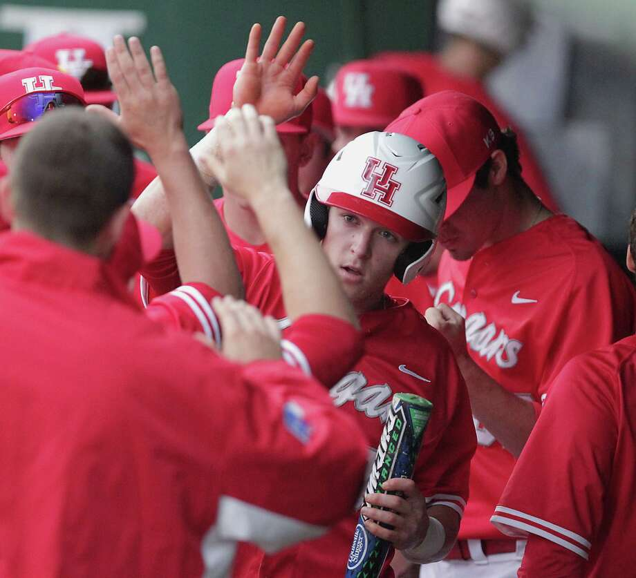 Kyle Survance of the Cougars celebrates in the dugout after scoring a run against Texas during the second inning. Photo: James Nielsen, Houston Chronicle / © 2013 Houston Chronicle