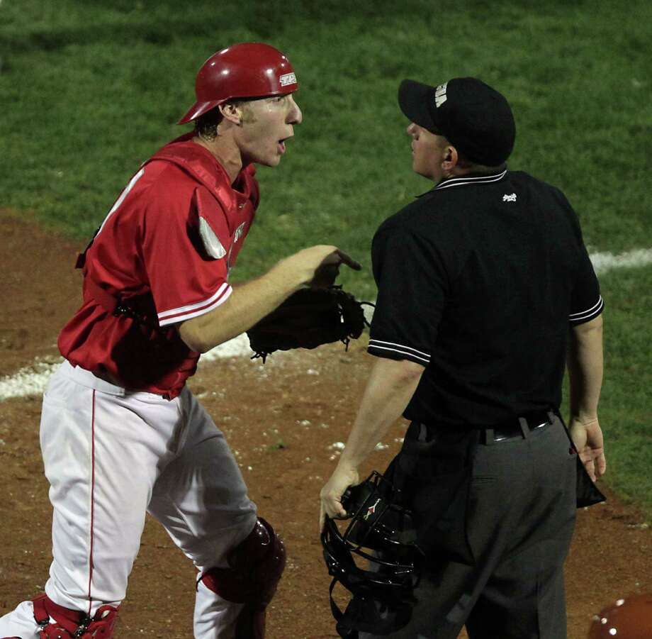 UH catcher Caleb Barker argues a call with home plate umpire Chuck Busse after a UT player is called safe at home plate during the sixth inning. Photo: James Nielsen, Houston Chronicle / © 2013 Houston Chronicle