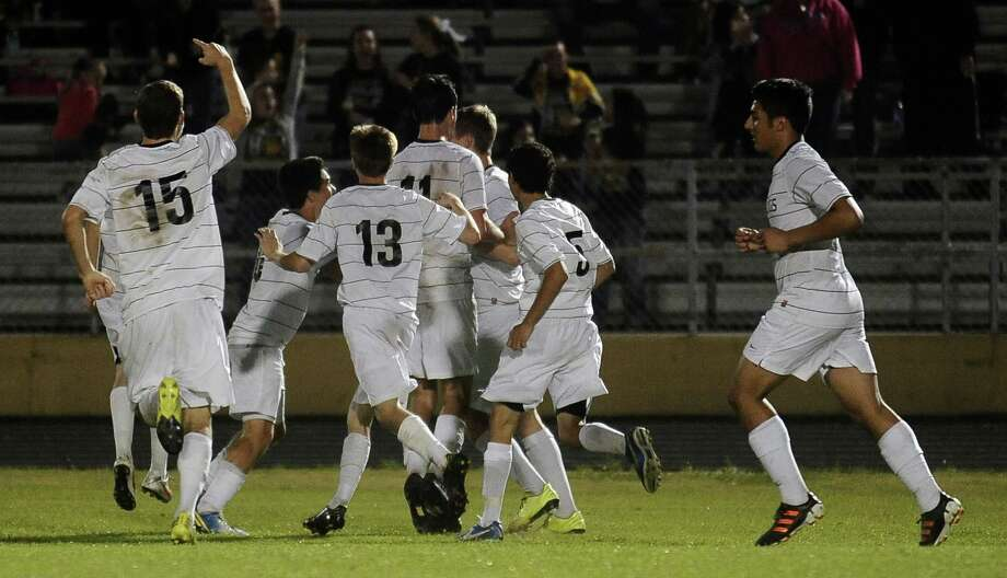 Nederland teammates join Tanner Noel to celebrate a goal in overtime during the Port Neches- Groves District 38-4A championship boys soccer game against Nederland on Tuesday, March 19, 2013, at Bulldog Stadium. Photo taken: Randy Edwards/The Enterprise Photo: Randy Edwards