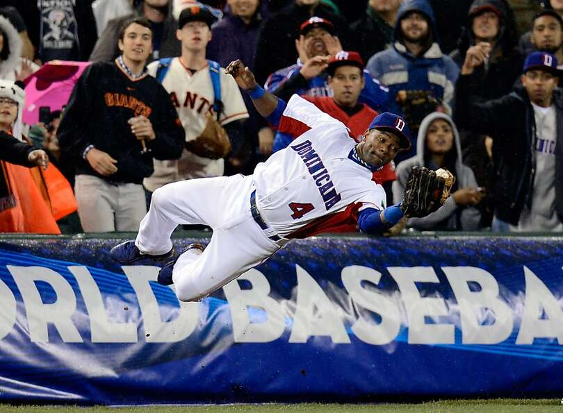 Miguel Tejada of the Dominican Republic dives to make a catch in foul territory in the seventh in