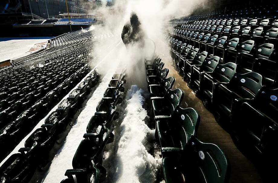 Barry Maddox sprays thick layers of snow and ice off the seats of Target Field in Minneapolis, Minn., on Tuesday, March 19, 2013. Crews used high-pressure heated water to clean snow and ice from the seats of the baseball field in preparation for the Minnesota Twins' opening day baseball game against the Detroit Tigers on April 1. (AP Photo/The St. Paul Pioneer Press, Ben Garvin) Photo: Ben Garvin, Associated Press