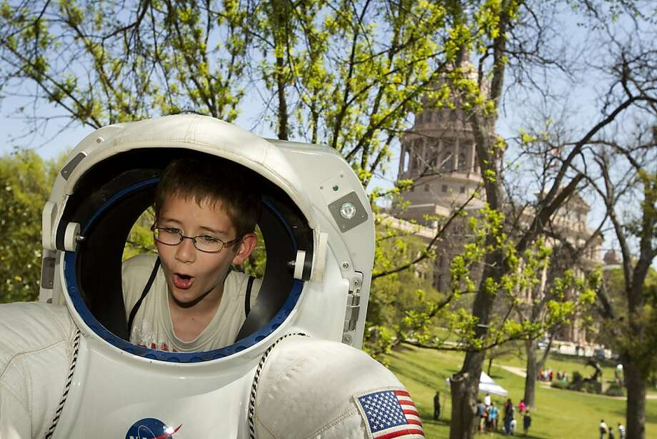 "Evan Harper, 9, climbs into the back of a real space suit at the Capitol in Austin, Texas, on Tuesday March 19, 2013. The space suit was part of a NASA exhibit ""Driven To Explore,"" which featured one of only eight moon rocks that the public can touch, and an autograph session with NASA astronaut Peggy Whitson. The activities were in conjunction with Space Day at the Capitol, which was part of Space Week Texas. (AP Photo/Austin American-Statesman, Jay Janner) Photo: Jay Janner, Associated Press"