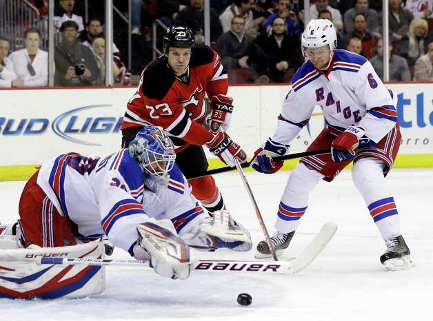 New York Rangers goalie Henrik Lundqvist, left, of Sweden, dives at the puck as New Jersey Devils center David Clarkson, center, and defenseman Anton Stralman, of Sweden, look on during the second period of an NHL hockey game, Tuesday, March 19, 2013, in Newark, N.J. (AP Photo/Julio Cortez) Photo: Julio Cortez