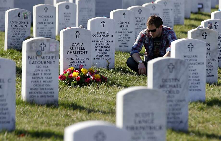 Ryan Lamke of Washington, sits by the grave of his fellow U.S. Marine, Cpl. Benny G. Cockerham III, in Section 60 of Arlington National Cemetery Tuesday, March 19, 2013, in Arlington, Va. Lamke visits his friends grave about once a month. Capt. Tyler Swisher, Navy Petty Officer 3rd Class Chris Thompson, and Marine Lance Cpl. Kenneth Butler also died with Cocherham when their Humvee was attacked by an improvised explosive device. March 20, 2013, marks the 10th anniversary of the U.S.-led invasion of Iraq. (AP Photo/Alex Brandon) Photo: Alex Brandon, Associated Press