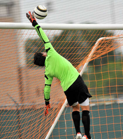 Reagan goalie Mauricio Alba deflects a Churchill shot during the first half of their District 26-5A championship match Tuesday evening. Photo: Robin Jerstad, For The San Antonio Express-News
