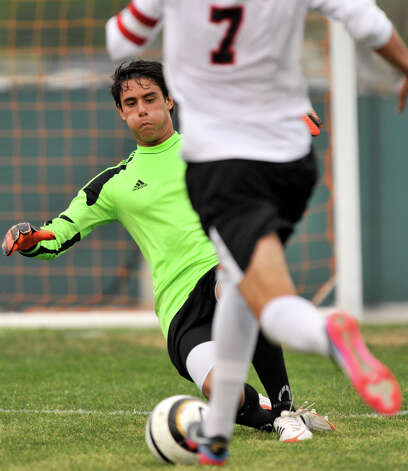 Reagan goalie Mauricio Alba slides to block a shot by Churchill's Gerardo Hernandez during the first half of their District 26-5A championship match Tuesday evening. Photo: Robin Jerstad, For The San Antonio Express-News