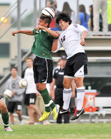 Reagan's Christian Dwarica (21) and Churchill's John Mendoz battle for the ball during their District 26-5A championship match Tuesday evening. Photo: Robin Jerstad, For The San Antonio Express-News