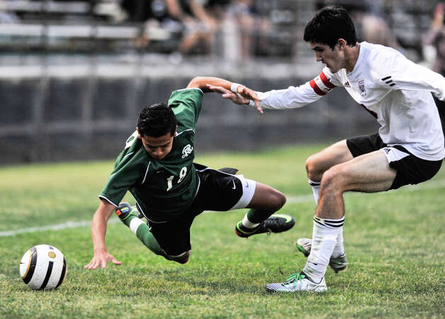 Reagan's Alan Ramos (18)  falls as he battles Churchill's Brendan Severyn for the ball during their District 26-5A championship Tuesday evening. Photo: Robin Jerstad, For The San Antonio Express-News