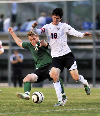 Reagan's German Lopez (10) battles Churchill's Brendan Severyn (18) for the ball during their District 26-5A championship match Tuesday evening. Photo: Robin Jerstad, For The San Antonio Express-News