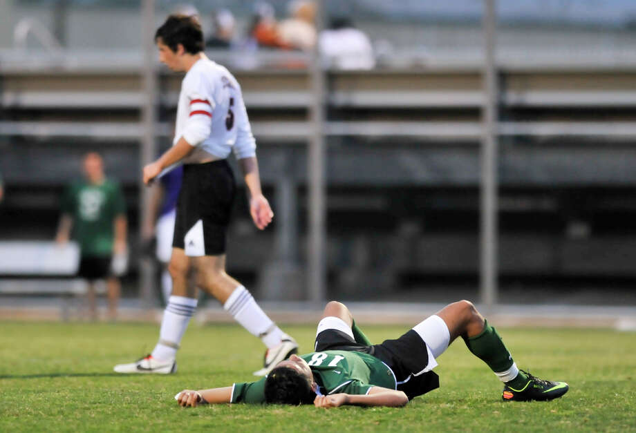 An exasperated Alan Ramos of Reagan lies on the pitch after missing a shot as time ran out at the end of the first half of the District 26-5a championship match versus Churchill Tuesday evening. Churchill's Harrison Herzberg walks away. Photo: Robin Jerstad, For The San Antonio Express-News