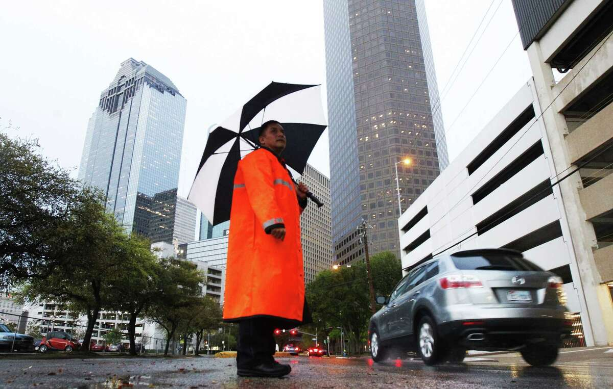 Officer C.C. Hernandez shields himself from the rain as he directs traffic on Dallas Street.