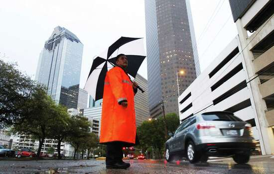 Officer C.C. Hernandez shields himself from the rain as he directs traffic on Dallas Street. Photo: Cody Duty / Houston Chronicle